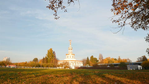 White historic building in the park at VDNH. Blue sky and yellow trees around Live Action