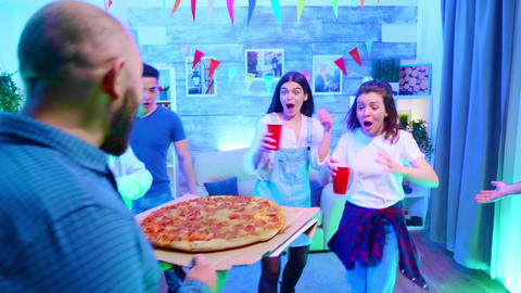 Follow shot of young man arriving at the party with delicious pizza Live Action
