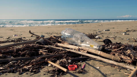 Plastic bottle garbage on polluted beach over sea waves motion background, 4k Live Action