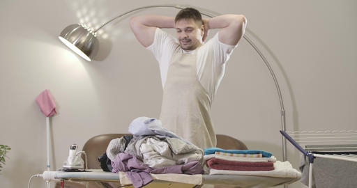 Adult Caucasian man holding head with hands as looking at pile of clothes lying Live Action