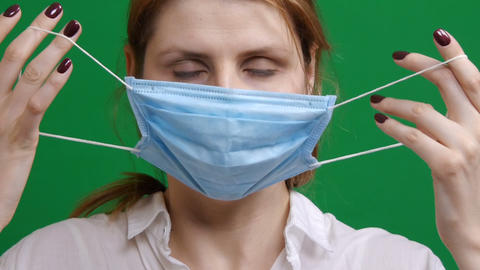 Girl puts on a protective medical mask. In the panic of the epidemic virus Live Action