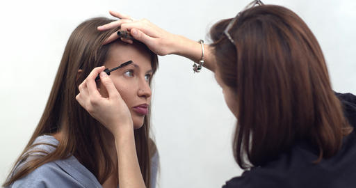professional makeup artist applies makeup, eye shadow for brown eyebrows with a Live Action