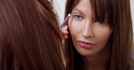 Professional makeup artist does makeup of young model. Close-up view of make-up Live Action