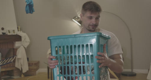 Young brunette Caucasian man holding laundry basket with dirty clothes and Live Action