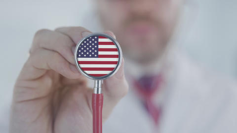 Doctor holds stethoscope bell with the American flag. Healthcare in the USA Live Action