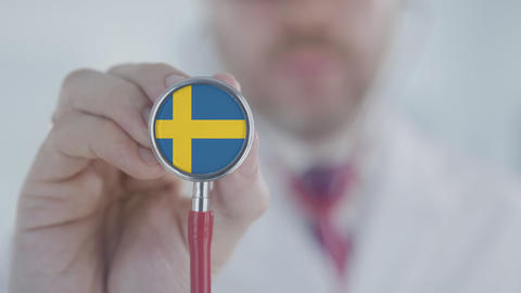 Medical doctor holds stethoscope bell with the Swedish flag. Healthcare in Live Action