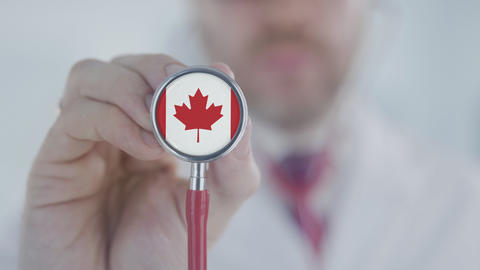 Physician holds stethoscope bell with the Canadian flag. Healthcare in Canada Live Action