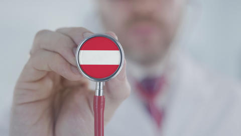 Medical doctor uses stethoscope with the Austrian flag. Healthcare in Austria Live Action