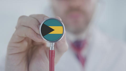 Physician uses stethoscope with the Bahamian flag. Healthcare in the Bahamas Live Action