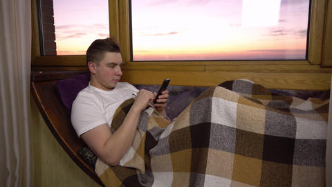 A young man is texting on the phone. A man lies on a window sill by the window Live Action