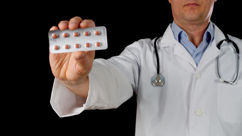 Doctor hand in white coat holding tablet blister front camera isolated on black Live Action
