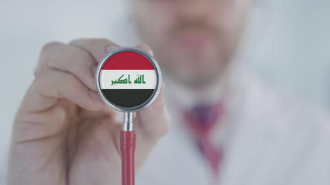 Doctor listening with the stethoscope with flag of Iraq. Iraqi healthcare Live Action