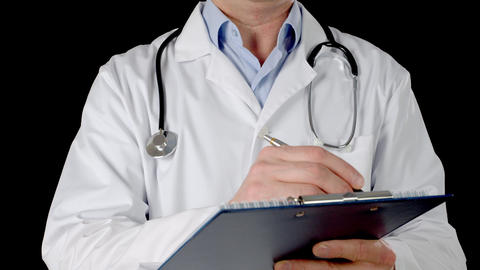 Doctor hand writing on clip board isolated on black background. Close up Live Action