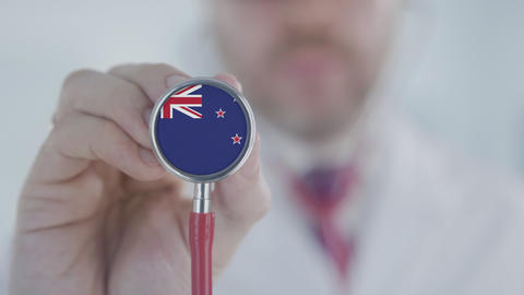 Medical doctor holds stethoscope bell with the national flag. Healthcare in New Live Action