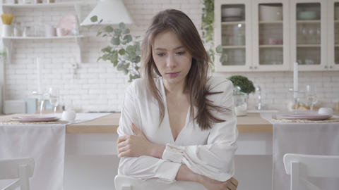 Portrait of beautiful Caucasian girl sitting in stylish kitchen and thinking Live Action