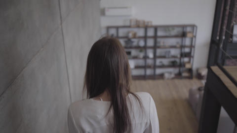 Back view of young brunette Caucasian woman walking down the stairs indoors Live Action