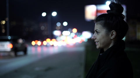 Lonely woman smiling while waiting on bus stop, talking with bluetooth handsfree Live Action