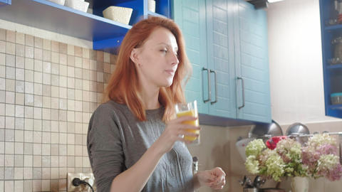 Beautiful girl drinking fresh orange juice from glass. Happy woman drinking Live Action