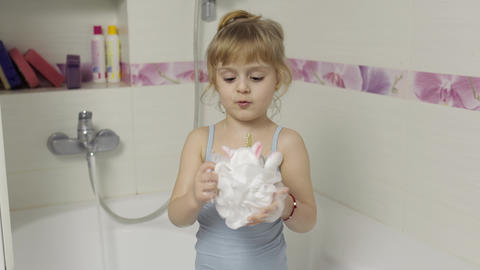 Cute blonde girl takes a bath in swimwear. Little child, 4 years old. Hygiene Live Action