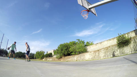 Two guys playing basketball on a clear summer day Live Action