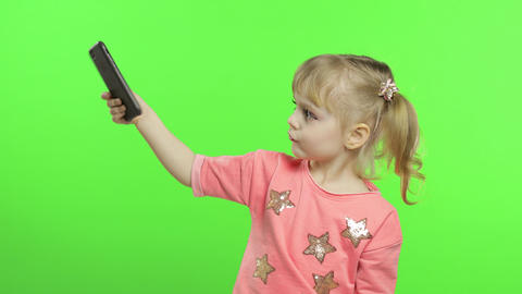 Little girl using smartphone. Child with smartphone making photos and selfies Live Action