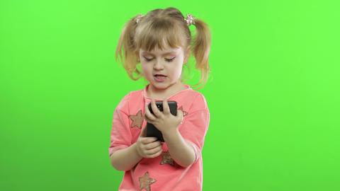 Little girl using smartphone. Portrait of child with smartphone texting, playing Live Action