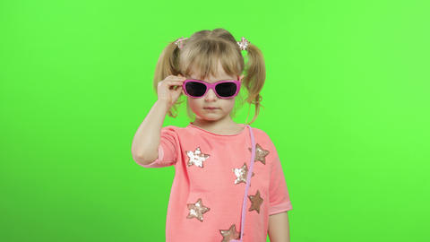 Positive girl in pink blouse and sunglasses dancing and posing. Chroma Key Live Action