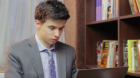 Businessman works on laptop, studying in library, freelancer Footage