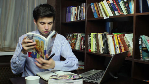 Man studying in library, reading French book, learning process Footage