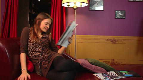 Young smiling woman relaxing, reading magazine, lounge hall Footage