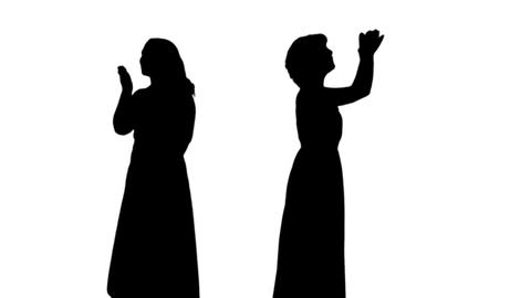 Silhouette of two woman waving their hands to audience Footage