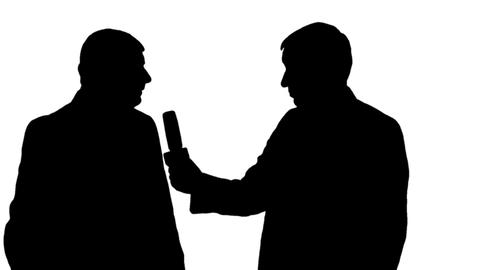 Silhouette of a male reporter interviews a man on black and white background Footage