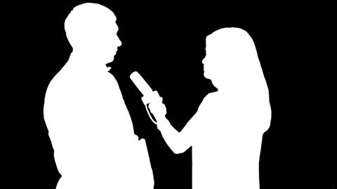 Silhouettes of a girl reporter interviewing a man on black & white background Footage