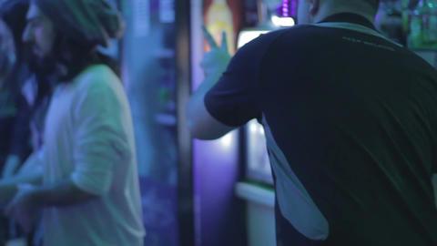 Barman serving drinks to nightclub guests, receiving orders Footage