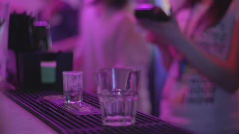 Bartender serving alcoholic drinks to clients at nightclub Footage