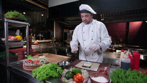 Sushi chef making sushi rolls with cucumber, restaurant kitchen Footage