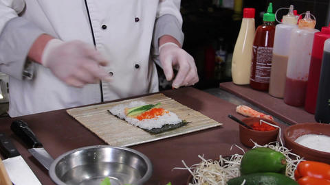 Chef making delicious sushi rolls with cucumber and red caviar Footage