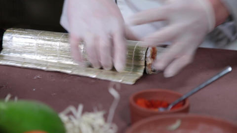Sushi chef shaping sushi rolls on bamboo mat, cooking process Footage