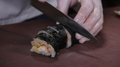 Sushi chef cutting sushi rolls with cucumber and red caviar Footage