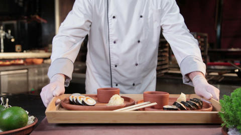Cook presenting ready dish, sushi rolls served on wooden plates Footage