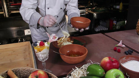 Chef flavoring delicious pancakes with cream and fruit jelly Footage