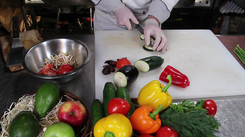 Restaurant cook cutting up fresh vegetables with a sharp knife Footage