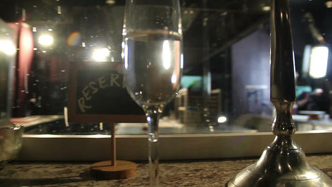 Champagne glass on reserved table, dim lights of restaurant Footage