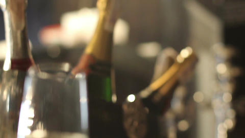 Champagne bottles in cooling bucket, glass of champagne on table Footage