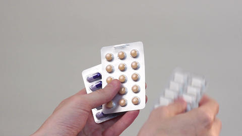 Hands holding colorful pills in blister packages, expensiveness Footage
