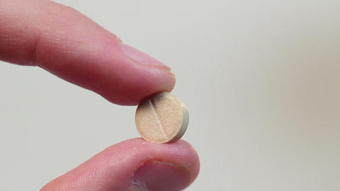 Ill person holding a pill with fingertips, hoping for recovery Footage