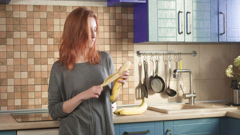 Attractive hungry redhead girl eats a big banana in the early morning on the Live Action