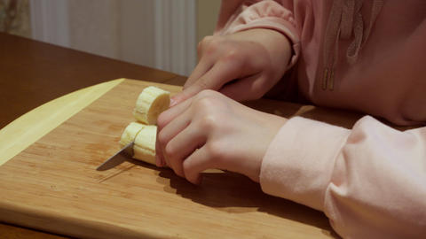 Female hands cutting by knife banana on wooden board. Close up female cook Live Action