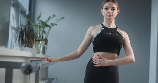 Attractive young woman stretches and practice near the ballet machine in the Live Action