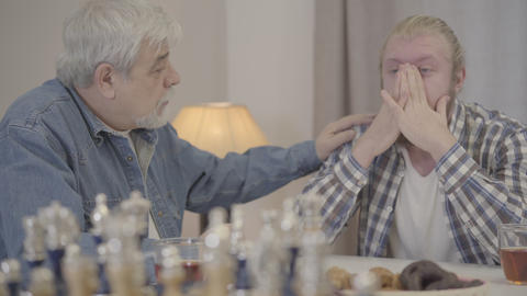 Close-up of wise old man calming down adult son at home. Portrait of elderly Live Action